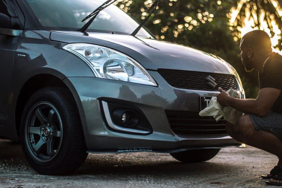 Photo d'un homme lavant la carrosserie de sa voiture illustrant l'article sur la bonne façon de nettoyer sa voiture